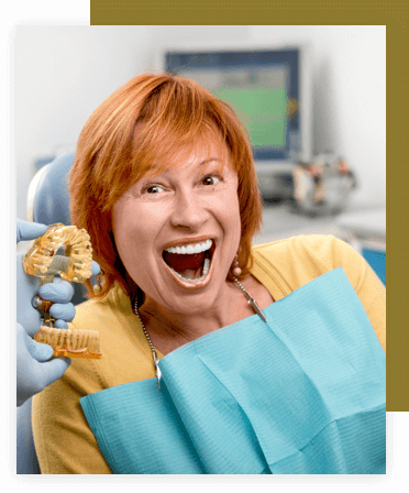 Woman with a big smile being shown a dental model.