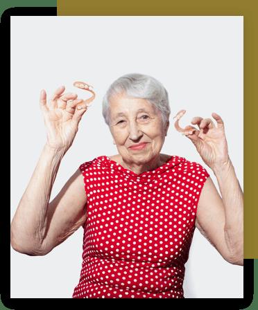 Elderly woman holding her dentures in her hands