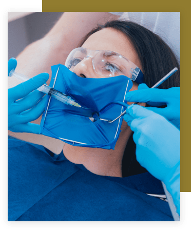 Woman with a mouth covering being injected with freezing before a root canal procedure