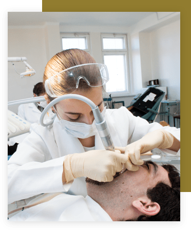 Dental hygienist cleaning a male patient's mouth.